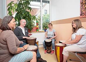 Auf dem Foto sind vier Menschen zu sehen, die zusammen auf großen Trommeln spielen und dabei Freude ausstrahlen. Im Hintergrund sind eine große Zimmerpflanze und ein helles Fenster zu sehen.