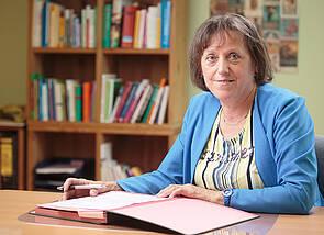 Die Vorsitzende des Vereins insel e.V., Frau Inge Kunze-Bechstädt: Frau Kunze-Bechstädt sitzt an einem Schreibtisch. Sie hat eine Unterschriftenmappe vor sich auf dem Tisch liegen.