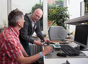 Auf dem Foto sind ein sitzender Mann und ein halb zu ihm herabgebeugter zweiter Mann an einem Computerarbeitsplatz zu sehen.