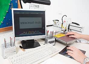 Fräsmaschine mit PC: Ein Computer zeigt auf dem Bildschirm, welcher Text gerade auf ein gelbes Schild gefräst wird. Ein Teil der Fräsmaschine und das Schild sind rechts erkennbar