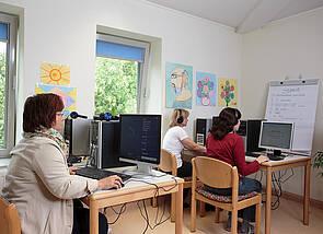 Gruppenraum mit PC-Ausstattung für Cogpack: An vier PCs sitzen Personen mit Kopfhörern, die konzentriert arbeiten. Im Hintergrund ist ein Flipchart zu sehen.