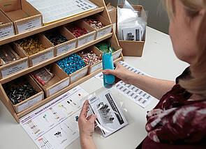 Eine Person sitzt an einem Tisch. Auf dem Tisch sind viele kleine Schütten zu sehen, die unterschiedliche elektronische Bauteile enthalten. Die Person heftet gerade eine durchsichtige Tüte zu, die mit diesen Teilen befüllt wurde.