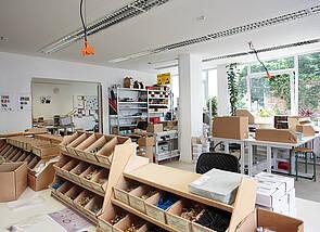 Werkstatt: Auf den Arbeitstischen sind mehrere Schütten mit elektronischen Bauteilen aufgebaut. Der Blick geht Richtung Fenster und gibt den Blick auf die begrünte Grundstücksmauer frei. An der linken Wand neben dem Fenster sind Regale zu sehen und der Durchgang in den Nebenraum der Werkstatt.