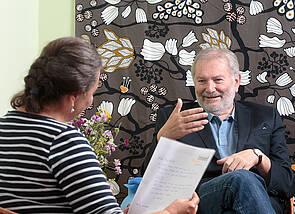 Beratungsgespräch: Eine Frau und ein Mann sitzen sich gegenüber. Der Mann lächelt und erklärt etwas, eine Hand ist angehoben und unterstreicht dies. Die Frau ist von hinten zu sehen; sie hat einen Brief in der Hand und hört aufmerksam zu. Im Hintergrund ist ein Stück der lindgrünen Wand und ein Stück einer Blumentapete zu sehen.