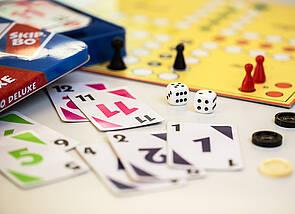 Spiele: Skippo, Mensch-ärgere-dich-nicht und Spielsteine eines Mühlespiels sind zu sehen.