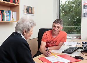 Beratungsgespräch: Zwei Menschen sitzen sich an der Ecke eines Schreibtisches gegenüber. Ein Mann erklärt etwas zu den Unterlagen, die auf dem Tisch liegen, die Frau hört ihm zu. Im Hintergrund ist ein großes Fenster zu sehen, durch das man ins Grüne blickt.