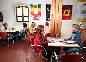 insel-café in der Stadtbücherei: Es ist der Sitzbereich des insel-cafés zu sehen. An kleinen, viereckigen Esstischen sitzen sich je zwei Menschen gegenüber, essen etwas und unterhalten sich.
