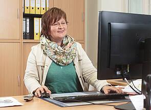 Im Büro: Eine Frau sitzt vor einem PC an einem Büroschreibtisch und arbeitet.