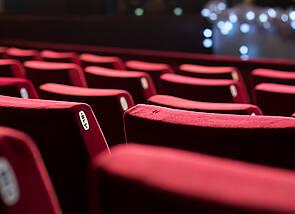 Es sind mehrere Reihen mit rotem Stoff bezogene Kinosessel zu sehen. Die Kinoleinwand ist im Hintergrund zu erahnen.