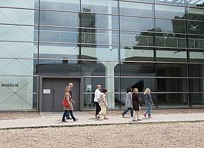 """Auf dem Foto spaziert eine kleine Gruppe von sieben Personen an einer überdimensionalen Glasfront vorbei. Links ist die Aufschrift """"Museum"""" zu lesen."""