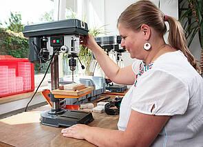 Bohrmaschine: Eine Frau sitzt an einem Arbeitstisch und bedient eine Tischbohrmaschine.