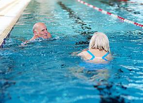 Das Foto zeigt einen Herrn und eine Dame im Schwimmerbecken eines Schwimmbads.