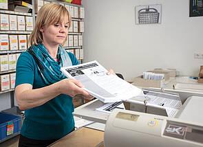 Falzmaschine: Eine Frau gibt einen Stapel Blätter in die Falzmaschine, die auf der rechten Bildseite in Teilen erkennbar ist. Im Hintergrund sind Arbeitsregale zu sehen, in denen beschriftete Kartons stehen.