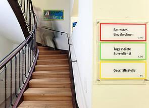 """Treppenaufgang des Standorts an der Esplanade 1: Im Zentrum des Bildes ist eine breite, gewundene Holztreppe zu sehen. Rechts im Bild sind Hinweisschilder zu erkennen, auf denen """"Betreutes Einzelwohnen"""", """"Tagesstätte/Zuverdienst"""" und """"Geschäftsstelle"""" steht."""