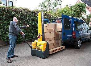 Hochhubwagen: Ein Mann bedient einen gelben Hochhubwagen und lenkt ihn in Richtung des zu beladenden Busses. Ein zweiter Mann steht auf der Ladefläche des Busses und nimmt die Pakete entgegen.