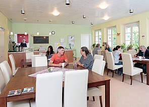 Cafeteria Esplanade: In einem großen, in hellem Gelb und lindgrün gehaltenen Raum, sitzen an verschiedenen Tischen verteilt Besucher und Besucherinnen der Cafeteria. Einige unterhalten sich oder lesen etwas. Im Hintergrund ist eine Theke zu sehen, auf der Kaffeekannen stehen. An der Wand hängen Programmhinweise.
