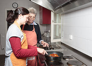 In der Küche: Zu sehen ist eine Herdzeile. Jemand brät etwas in einer Pfanne an und wird dabei von einer zweiten Person angeleitet.