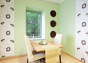 Beratungsraum: Auf dem Bild ist ein Tisch mit zwei gegenüberliegenden hochlehnigen Stühlen zu sehen. Der Raum strahlt Ruhe aus. Die Wand ist in lindgrün gehalten; unterbrochen von zwei Tapetenbahnen, die ein dezentes Blumenmuster haben.