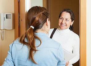Eine Frau im blauen Hemd mit Pferdeschwanz, die nur von hinten zu sehen ist, öffnet ihre Wohnungstür. Sie begrüßt eine zweite Frau, die freundlich lächelnd vor der Tür steht. Es ist erkennbar, dass diese Frau eine Tasche und einige Papiere dabeihat.