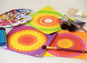 Auf dem Foto sind Pinsel, Farben und einige leuchtende kleine Bilder zu sehen, die symbolisch für die kreativen Arbeiten stehen.