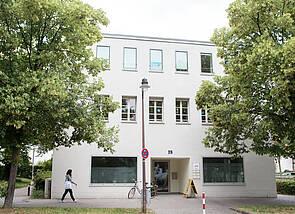 Das Bild zeigt die Vorderansicht des Hauses an der Esplanade 1. Das Haus ist weiß gestrichen, es hat viele Fenster, links und rechts wird es umrahmt von zwei Bäumen.