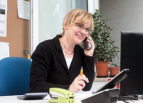 Telefonat: Eine Frau sitzt mit Kugelschreiber in der Hand an einem Schreibtisch. Sie telefoniert.