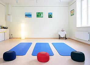 Yoga-Raum: Es ist ein Raum mit hellen Wänden zu sehen. Auf dem Boden liegen nebeneinander drei blaue Gymnastikmatten und je ein verschiedenfarbiges Sitzkissen. An der Wand hängen einige ruhige Aquarelle, vom seitlichen Fenster strömt Licht in den Raum, der dadurch eine helle, freundliche Ausstrahlung bekommt.