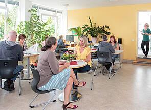 Das Foto zeigt einen Blick in einen großen, hellen, gelb angestrichenen Raum mit großen Fensterflächen. An den Tischen sitzen locker verteilt einige Männer und Frauen und unterhalten sich. Im Hintergrund ist eine Person zu sehen, die durch die Balkontür indsd