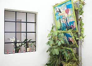 Vertikaler Garten: Links ist ein Treppenhausfenster zu sehen, das den Blick auf den dahinterliegenden Gang erlaubt. Rechts ist an der Wand eine Stahlkonstruktion zu sehen, in deren aufgefächerten Blumenkästen grüne Zimmerpflanzen wuchern.